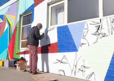 David Teng Olsen adds illustrations to the mural. Illustrations were based on the people Olsen encountered during the 8 days he was painting the piece. Photo by Jeremy Fraga